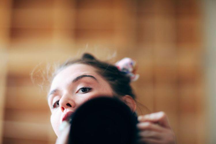 Portrait of woman holding mirror