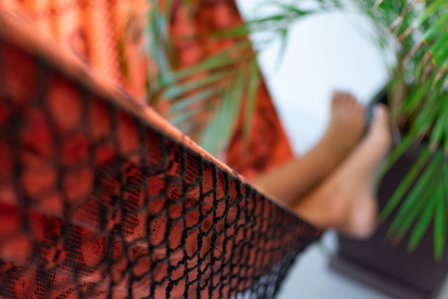 One Person Human Body Part Human Leg Adult Body Part Selective Focus Lifestyles Women Low Section Day Real People Focus On Foreground Unrecognizable Person Hammock Textile Leisure Activity Human Foot Close-up Relaxing Orange Color Sleep On Hammock Sleeping Leasure Free Time