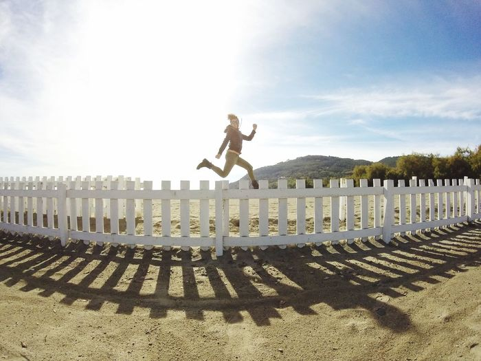 Full length of woman jumping over fence at beach