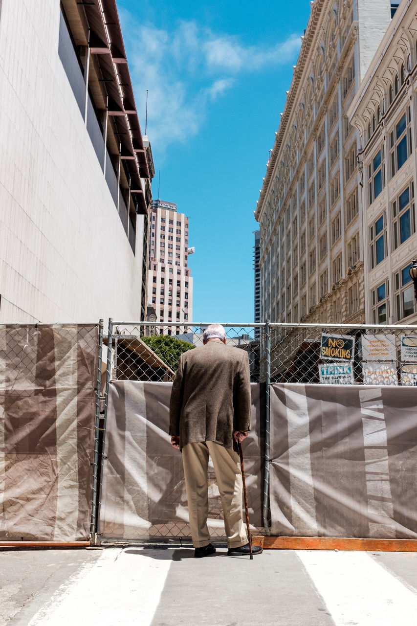 architecture, built structure, building exterior, full length, day, rear view, real people, sky, people, city, men, nature, sunlight, building, lifestyles, cloud - sky, footpath, shadow, adult, outdoors