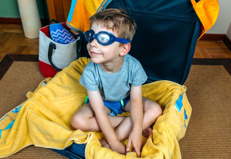 Boy wearing swimming goggles while sitting in suitcase at home