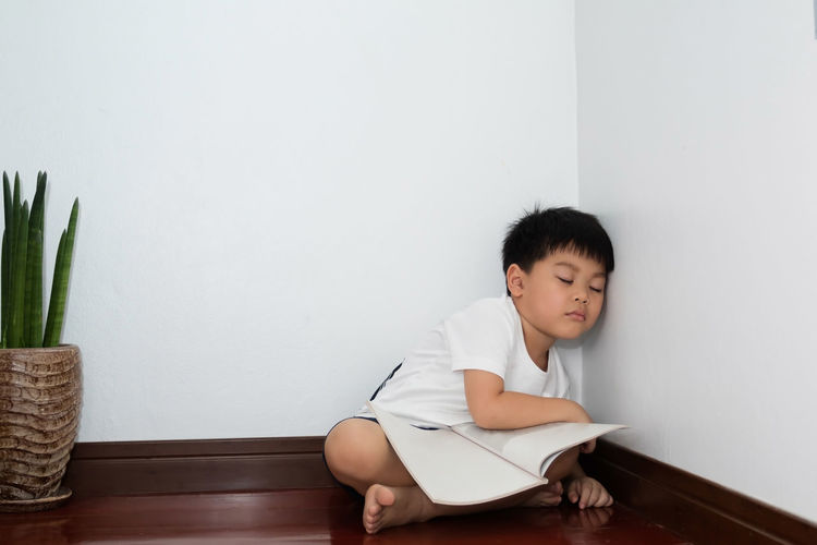 Boy looking away while sitting on wall at home