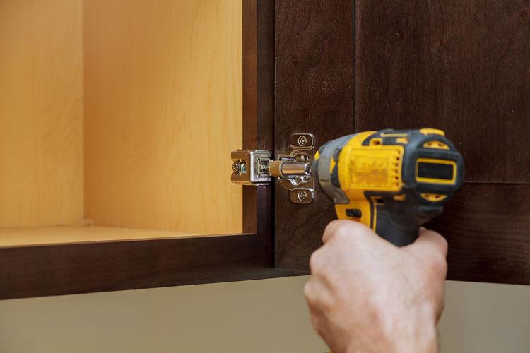Cropped Hand Using Nail Gun At Home