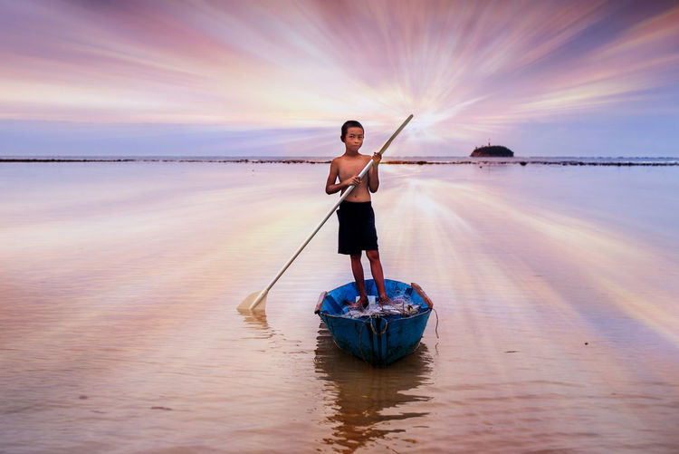 Boy rowing boat in sea against sky during sunset