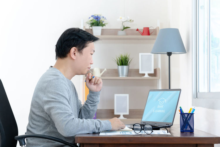 Side view of young man using laptop on table