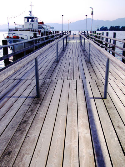 Absence Boardwalk Day Diminishing Perspective Fraueninsel Harbor No People Ocean Outdoors Pier Plank Sea Sky Surface Level The Way Forward Tranquility Water Wood Wood - Material Wood Paneling Railing Boat Deck Nature Nautical Vessel