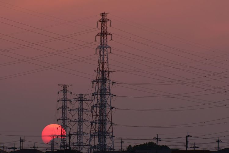 Low Angle View Of Electricity Pylons Against Sunset