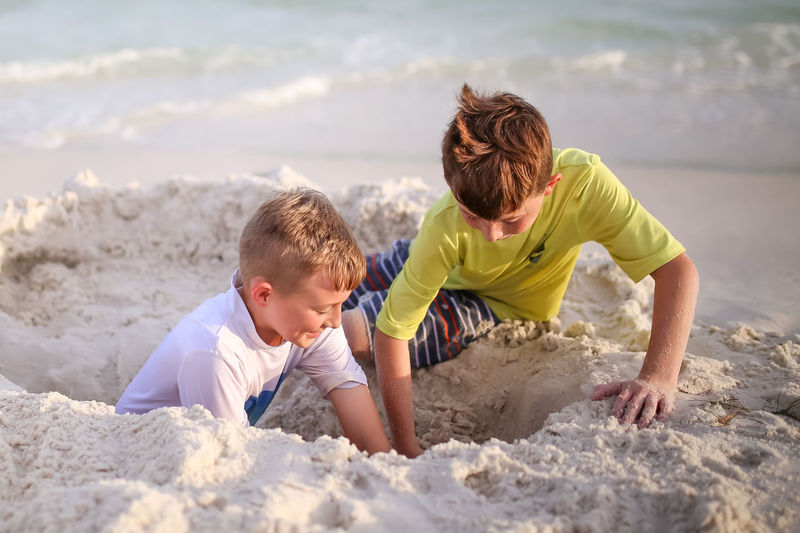 Brothers Digging Hole At Beach