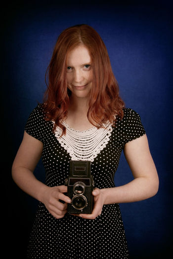 Portrait Of Young Woman Holding Camera Against Blue Background