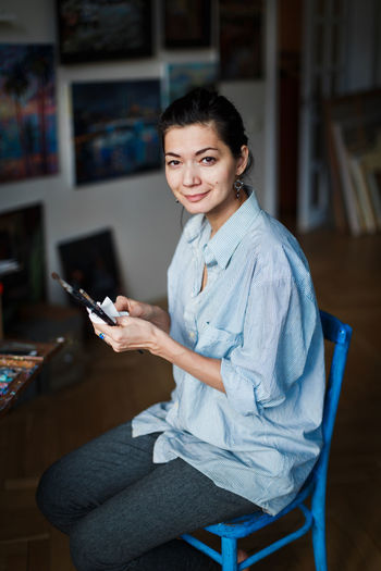 A young smiling brunette woman artist in her Studio is holding a brush. Near her easel, paintings and various art equipment. Sitting Looking At Camera One Person Smiling Indoors  Three Quarter Length Young Adult Casual Clothing Holding Adult Lifestyles Focus On Foreground Portrait Real People Furniture Artisan Artist Art Art Studio Painting Brush Leisure Activity Hobbies Woman Girl