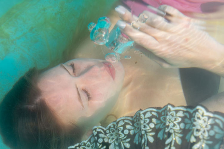 High angle view of woman holding wineglass while in swimming pool