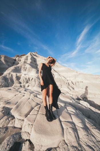 Full length of woman on rock against sky