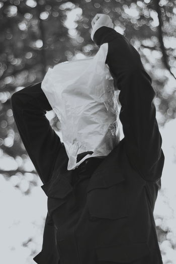 Man wearing plastic bag over face while standing against tree