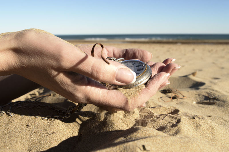 Cropped image of woman holding pocket watch on sand at beach against clear blue sky