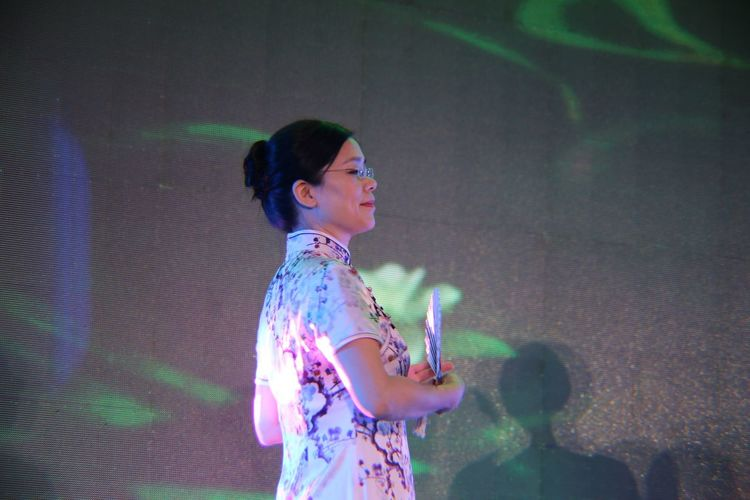 Woman holding handfan while standing on stage