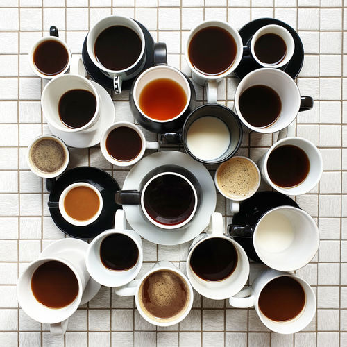 High angle view of multiple collection coffee cups on tiled table
