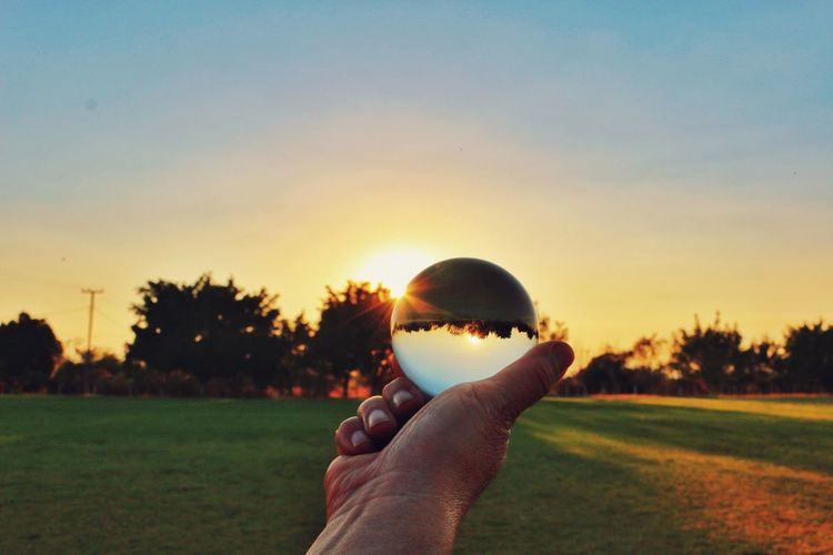 sunsets Crystal Crystal Ball Sphere Lensball Lensball Photography Photography Upside Down Human Body Part Human Hand One Person Personal Perspective Sunset People Silhouette Sky Grass Adult One Man Only Close-up