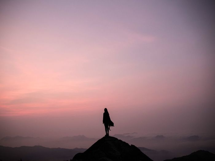 Silhouette woman standing on top of mountain against sky