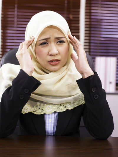 Business Stories Overworked Stress Close-up Day Front View Hand On Head Headache Headwear Hijab Human Hand Illness Indoors  Lifestyles Massage One Person Real People Tudung Uncomfortable Wireless Technology Young Adult Young Women