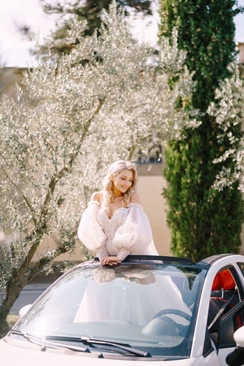 Bride standing in car outdoors