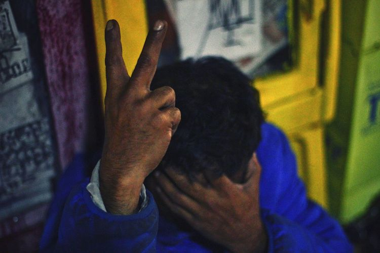 Close-up of man showing peace sign