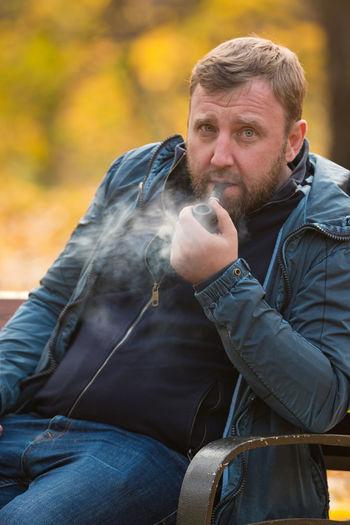 Portrait Of Mature Man Smoking While Sitting On Bench At Park