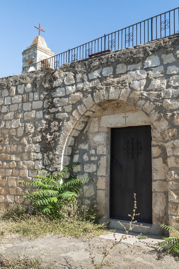 Bar'am, Israel, June 09, 2018 : The belfry and the side door in the functioning church of the Christian Maronites in the abandoned village Kafr Birim in the north of Israel Christian Maronites Church Cross God Jesus Christ Kafr Birim Abandoned Village Arabic Architecture Art Belfry Tower Bible Building Culture Day Heritage History Holy Israel Landmark Monument Old Pry Religion Symbol