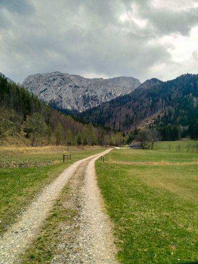 Dirt road amidst green landscape and mountains against sky
