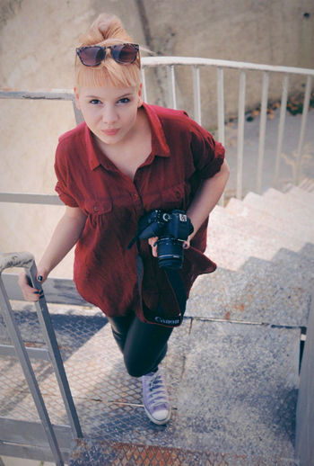 Portrait of young woman standing on railing