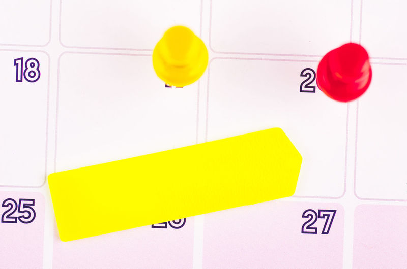 sticky paper and thumbtacks on calendar Communication Text Yellow Western Script No People Sign Close-up Number Indoors  Note Red Adhesive Note Reminder Information Paper Guidance White Color Letter Wall - Building Feature Door Message