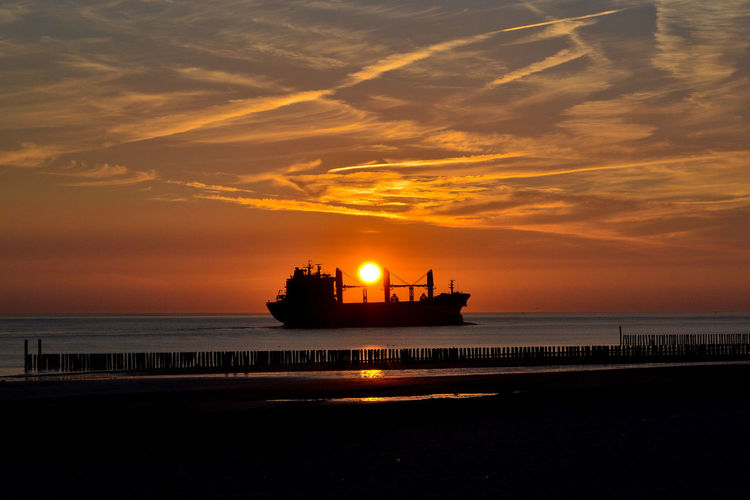 Silhouette ship in sea against sky during sunset