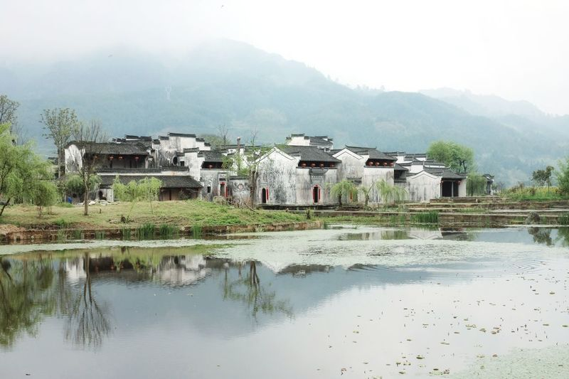 Houses by lake and buildings against sky
