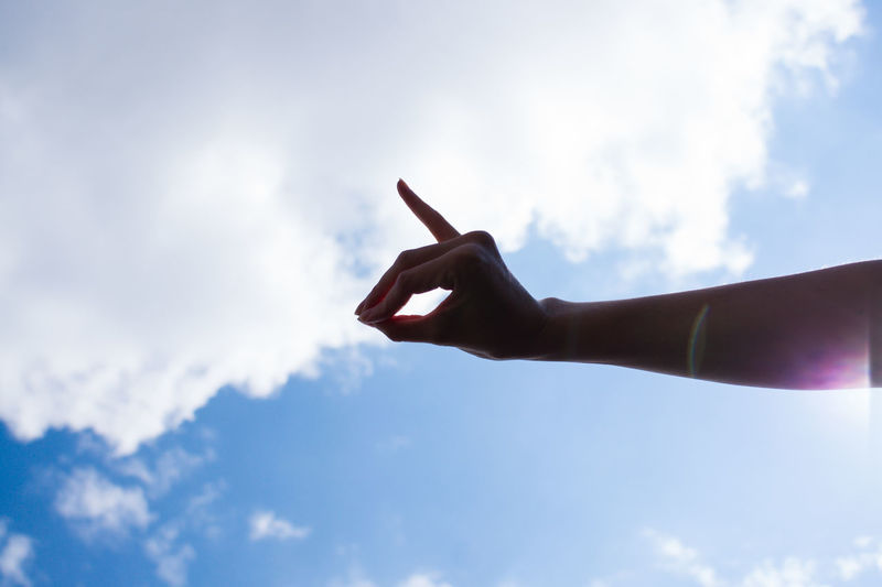 Low angle view of person hand against sky