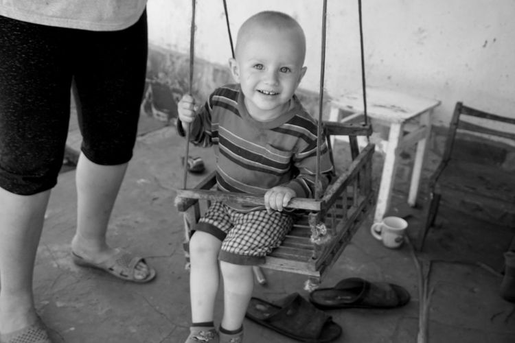 Portrait of boy smiling while sitting on swing