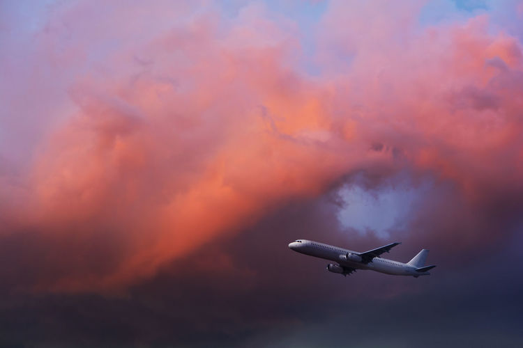Low angle view of airplane flying against sky during sunset