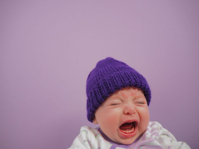 Close-up of crying baby against purple background