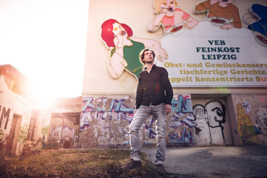 young man standing in front of the Leipziger Löffelfamilie Against The Light Casual Casual Look Leipzig Man Architecture Building Exterior Built Structure Day Front View Full Length Lifestyles Löffelfamilie Man Standing One Person Outdoors Portrait Real People Standing Sunset Veb Feinkost Young Adult