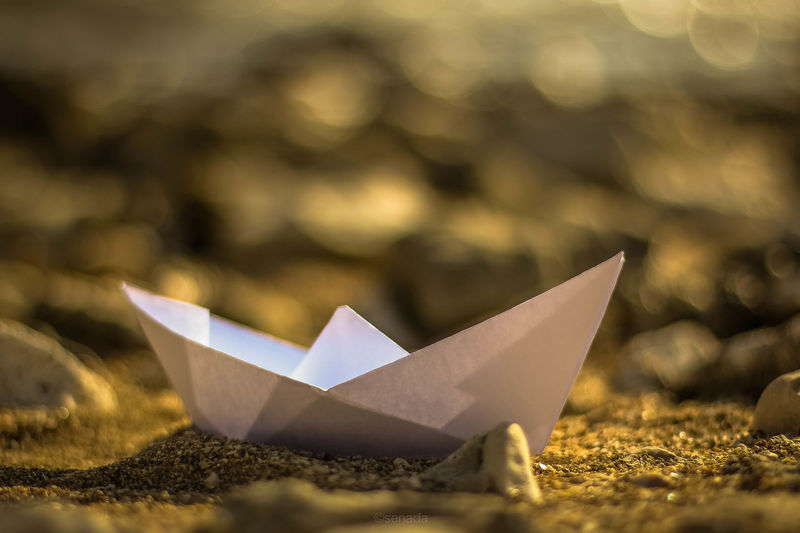 Close-up of paper boat on sand