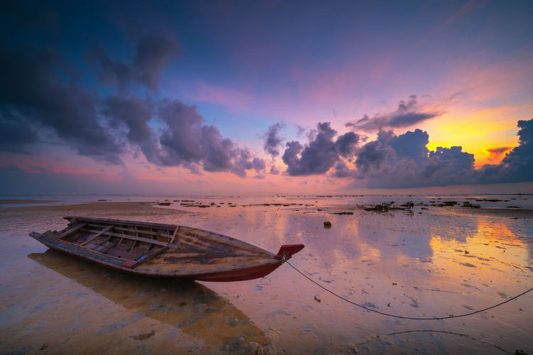 Abandoned rowboat moored on shore at beach against dramatic sky during sunset