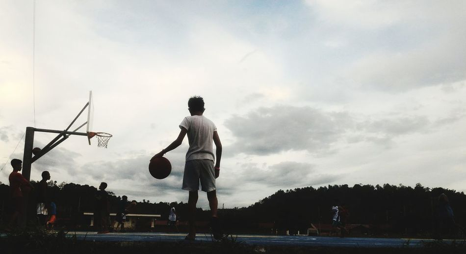 Group Of People Practicing Basketball Against Sky