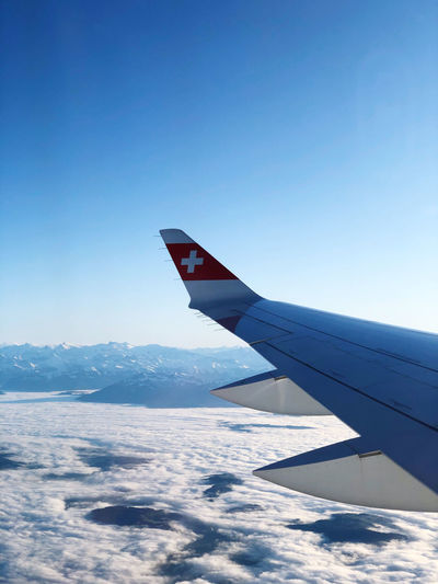 Airplane flying over snowcapped mountains against clear blue sky