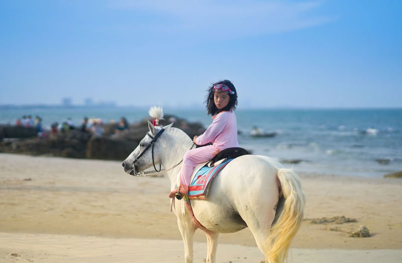 Full length of girl sitting on horse at beach against sky