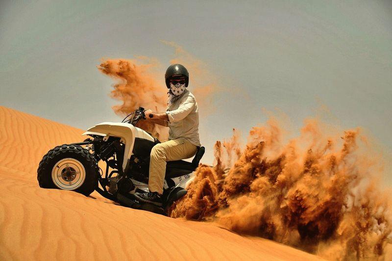 Man Riding Quadbike On Sand Against Sky