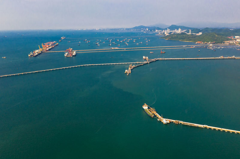 Seascape and oil station bridge with sailing shipping oil and gas on the green sea aerial view