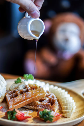 Close-up of person pouring honey on waffle
