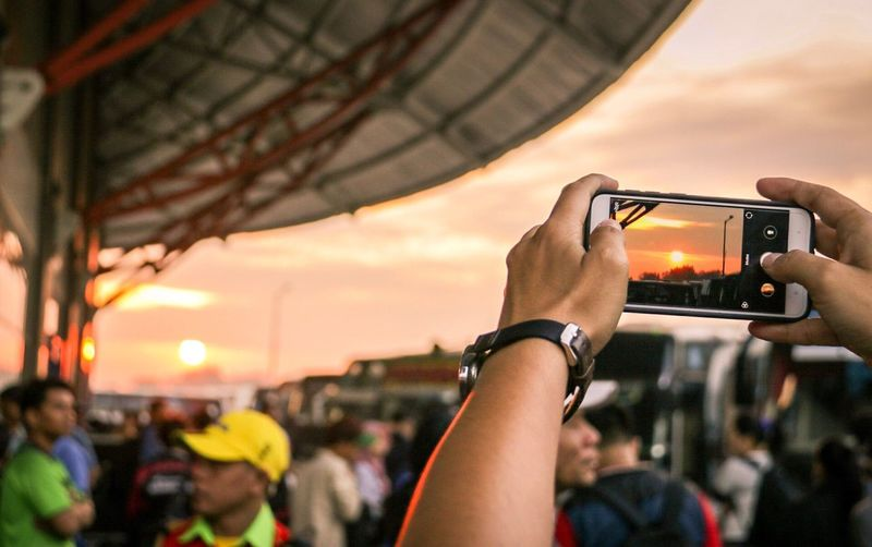 Close-up of woman photographing with mobile phone against sky