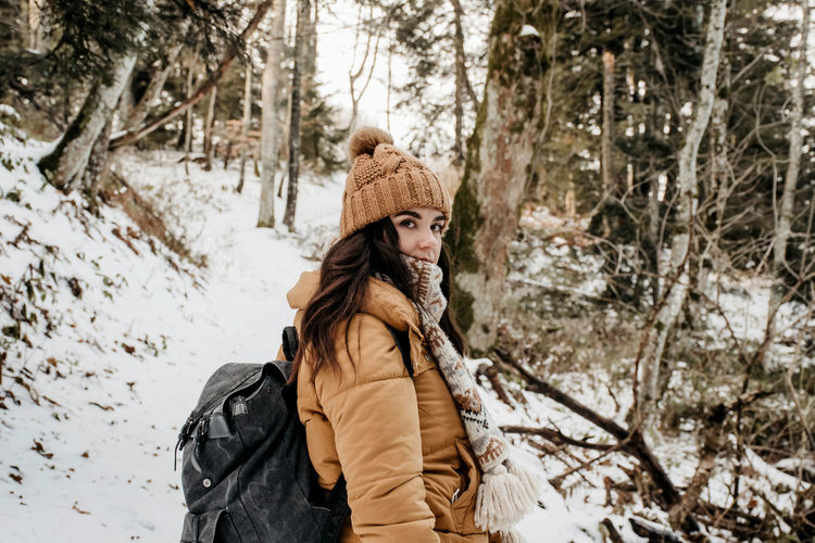 Woman wearing hat in forest during winter. backpack, hiking, snow.