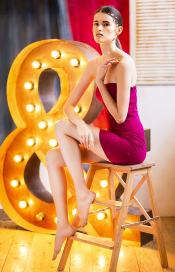 Full length of young woman sitting on seat