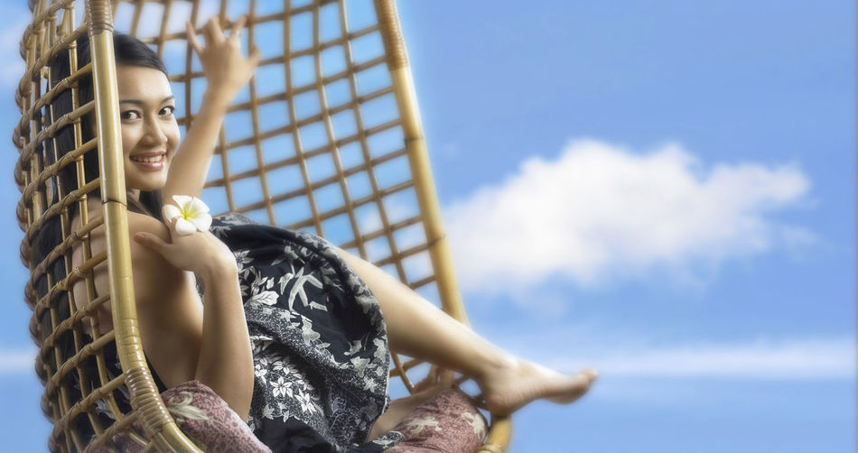 Close-Up Portrait Of Smiling Young Woman Sitting On Swing Against Sky