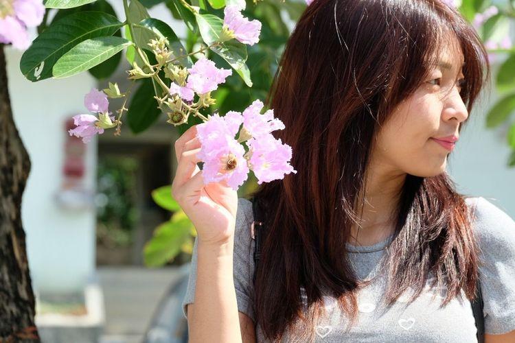 Woman Looking Away By Purple Flowering Plants
